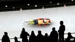 The German doubles team of Tobias Wendl and Tobias Arlt speed down the track during the luge team relay competition at the 2014 Winter Olympics, Feb. 13, 2014, in Krasnaya Polyana, Russia.