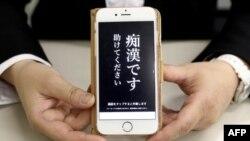 Keiko Toyamine, pejabat di departemen kepolisian Jepang, menunjukkan aplikasi untuk menakuti para penganiaya, di Tokyo, 13 Mei 2019. (Foto: AFP).