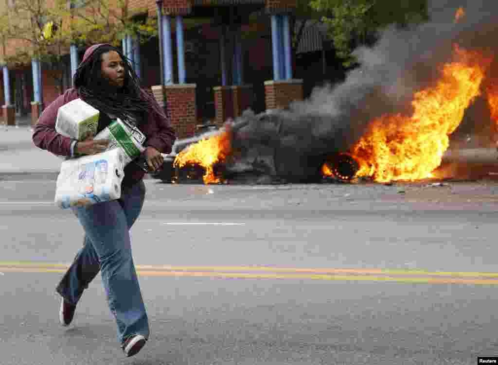 A woman with goods looted from a store runs past burning vehicles during clashes in Baltimore, Maryland, April 27, 2015.