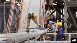 Oil workers work at Zubair oil field near Basra, 550 kilometers (340 miles) southeast of Baghdad, Iraq, Sunday, May 15, 2011.