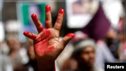 An anti-government protester raises a hand painted in red to symbolize bloodshed during a demonstration to demand the ouster of Yemen's President Ali Abdullah Saleh in the southern city of Taiz November 1, 2011.