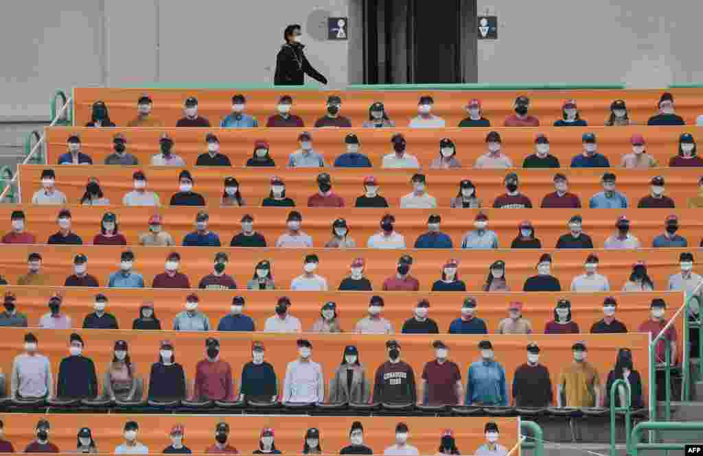 A man walks past banners depicting spectators in the stands prior to South Korea's new baseball season opening game between SK Wyverns and Hanwha Eagles in Incheon.