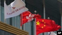 香港國泰航空公司總部大樓外公司旗幟在香港特區旗幟和中國國旗旁飄揚。 (2020年10月21日)