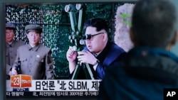 Raia wa Korea Kusini akiangalia ripoti za TV zikionyesha habari katika gazeti la Korea Kaskazini la Rodong Sinmun.