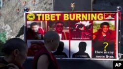 Poster shows pictures of Tibetan monks who have self-immolated since March, Dharmsala, India, Oct. 19, 2011.