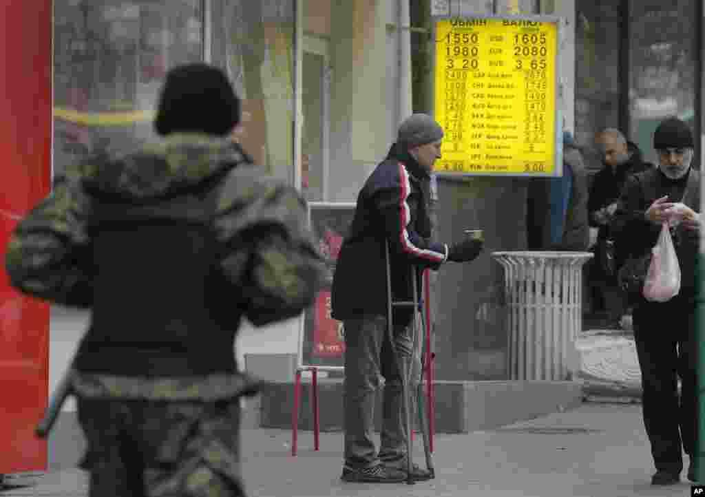 A man begs on a street near a currency exchange bureau in Kiev, Ukraine, Thursday, Nov. 13, 2014.