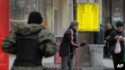 Чоловік просить милостиню біля пункту обміну валют у Києві, 13 листопада 2014 р.