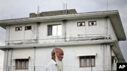 Seorang warga berjalan melintasi kompleks perumahan di Abbottabad, dimana pemimpin al-Qaida Osama bin Laden dilaporkan tewas dalam penggerebekan rahasia tentara AS, 5 Mei 2011 (Foto: dok).