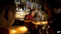 西藏日喀则扎什伦布寺的僧侣2019年7月19日在点亮寺庙松油。