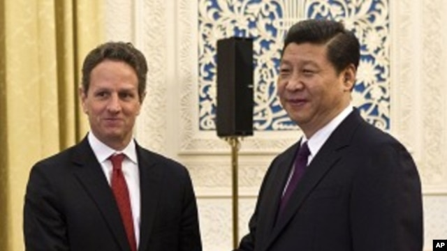 U.S. Treasury Secretary Timothy Geithner, left, shakes hands with Chinese Vice President Xi Jinping at the Great Hall of the People in Beijing, January 11, 2012