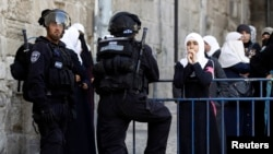 A Palestinian woman looks on as Israeli policemen prevent people from entering the compound which houses al-Aqsa mosque in Jerusalem's Old City April 16, 2014.