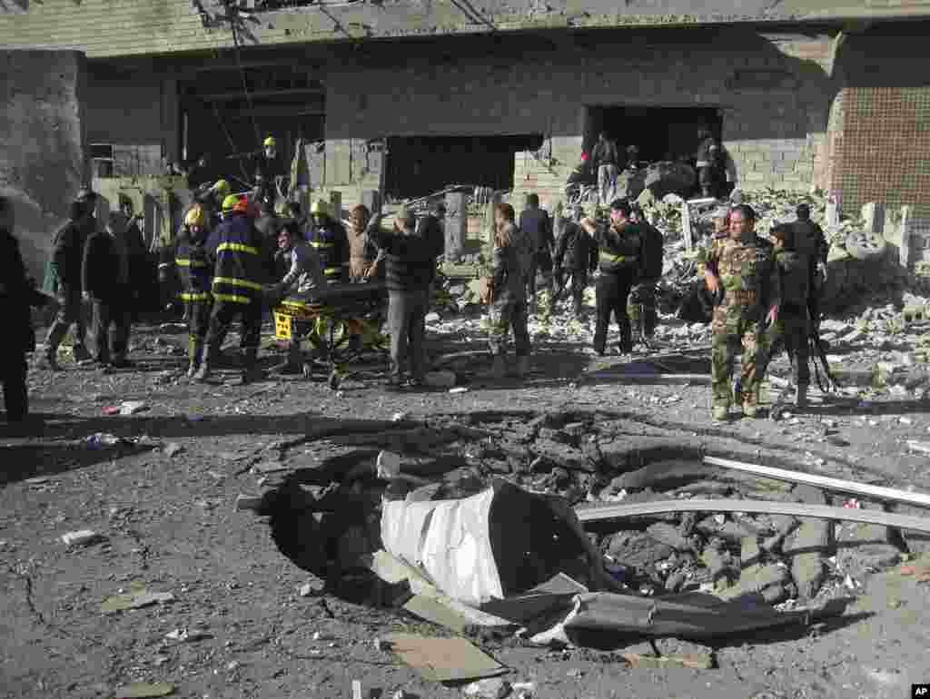 2013年2月3日,伊拉克平民和安全部队在巴格达以北290公里远的城市基尔库克检查地面上一个被汽车炸弹爆炸炸开的弹坑。