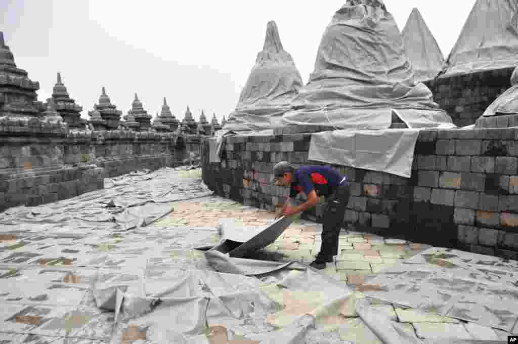 A worker spreads plastic sheets to cover Borobudur temple to protect from volcanic ash, from an eruption of Mount Kelud, in Magelang, central Java, Indonesia, Feb. 14, 2014.