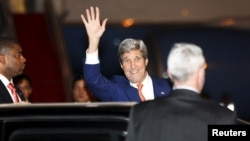 Ngoại trưởng John Kerry vẫy chào các nhà báo sau khi đặt chân tới sân bay quốc tế Phnom Penh hôm 25/1.