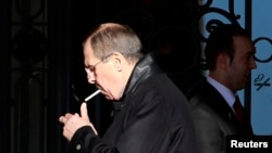 Sergey Lavrov lights a cigarette outside the Montreuz Palace Hotel in Geneva, Jan. 22, 2014.