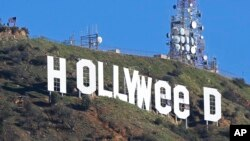 "The Hollywood sign in Los Angeles, California, is seen altered Jan. 1, 2017. Los Angeles residents awoke New Year's Day to find a prankster had changed the landmark sign to read ""HOLLYWEED."""