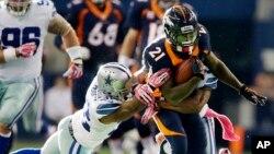 Ronnie Hillman (21) es atrapado por Barry Church de los Cowboys de Dallas, en emocionante juego de la NFL.
