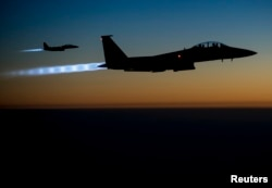 FILE - A pair of U.S. Air Force F-15E Strike Eagles fly over northern Iraq after conducting airstrikes in Syria, in this U.S. Air Force handout photo.