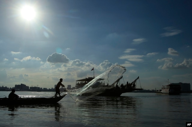 FILE - A fisherman casts his fishing net next to a ferry in the Mekong river near Phnom Penh, Cambodia, Tuesday, Dec. 1, 2015.