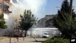 مأموران آتشنشانی در حال خاموش کردن آتش ناشی از انفجار خودروی بمبگذاری شده، شهر وان