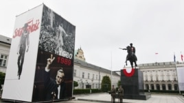 Pictures of Lech Walesa leading the 1980 strike that gave rise to the Solidarity freedom movement, top and of Prime Minister Tadeusz Mazowiecki flashing a v-sign in 1989, bottom on display in front of the Presidential Palace in Warsaw, Poland, June 2,
