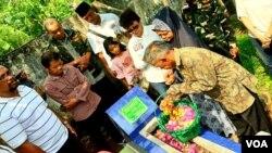 Orang tua dan adik almarhum Riyanto, berziarah ke makam bersama sejumlah komunitas. Riyanto gugur saat terjadi teror bom malam Natal 24 Desember 2000, di Gereja Eben Haezer, Kota Mojokerto (VOA/Petrus Riski).