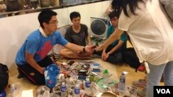 """Student volunteers offer a free phone charging service at """"Charging Corner"""" inside Hong Kong's occupied central business district. The students have adapted a multi-USB powerboard, and can charge up to 80 telephones from one electric socket, Oct. 8, 2014. (Ivan Broadhead/VOA)"""
