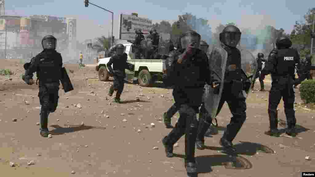 La police accourt après avoir lancé du gaz lacrymogène contre des manifestants qui ont répondu avec des jets des pierres à Ouagadougou, Burkina Faso.