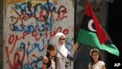 一名手拿反叛力量旗帜的妇女和她的女儿们走在利比亚首都的黎波里的街上