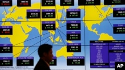 A man walks past a bank's electronic board showing the share indexes around the world at the Hong Kong Stock Exchange, Aug. 27, 2015.