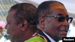 Zimbabwean President Robert Mugabe (R) and Prime Minister Morgan Tsvangirai arrive at a rally marking Zimbabwe's 31st independence anniversary celebrations in Harare, Zimbabwe, April 2011. (file photo)