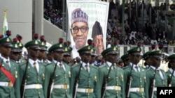 Des soldats nigérians devant un poster du président Mohammadu Buhari, à Abuja, le 29 mai 2015. (AFP PHOTO/PIUS UTOMI EKPEI)