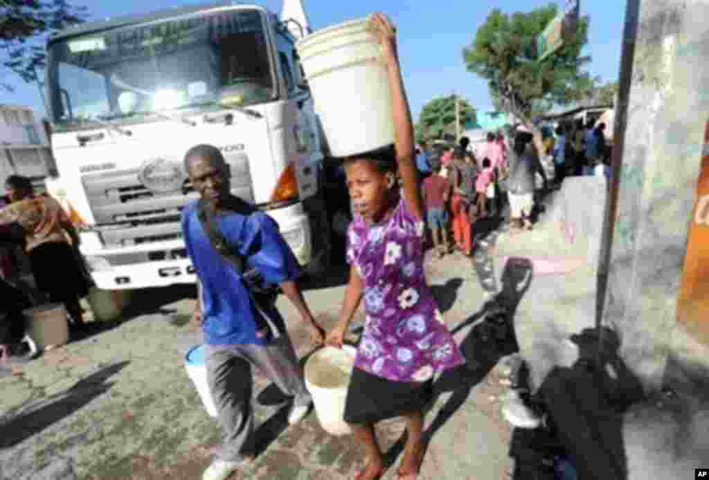 Haitians carry potable water supplied by a tanker in Port-au-Prince January 15, 2010. Despairing Haitians clawed by hand to seek survivors in the rubble of their homes as frustration grew at the trickle of aid Friday after a quake the Red Cross said may h