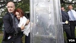 Seorang polisi Australia melindungi PM Julia Gillard dari demonstran yang tak terkendali di ibukota Canberra pada HUT Kemerdekaan Australia (26/1).