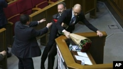 Oleh Barna, a Ukrainian lawmaker from the Block of Petro Poroshenko, second left, tries pull Ukrainian Prime Minister Arseniy Yatsenuk out from the podium during his speech at a parliamentary session in the Parliament in Kyiv, Ukraine, Friday Dec. 11, 2015.
