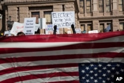 FILE - Demonstrators gather outside the Texas State Capitol in an attempt to influence the Republican electors from across the state to not vote for Donald Trump when they cast their formal ballots for president of the United States in Austin, Texas, Dec. 19, 2016.