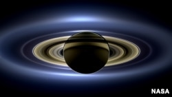 On July 19, 2013, NASA's Cassini spacecraft slipped into Saturn's shadow and turned to image the planet, seven of its moons, its inner rings -- and, in the background, our home planet, Earth.