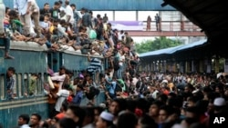 Bangladeshi Muslims make space for themselves on the roof of an overcrowded train to head home ahead of Eid al-Fitr as others wait at a railway station in Dhaka, Bangladesh, Thursday, Aug. 8, 2013. Hundreds of thousands of people working in Dhaka to make