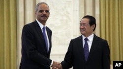 U.S. Attorney General Eric Holder, left, shakes hand with Chinese Politburo Standing Committee member Zhou Yongkang during a meeting at the Great Hall of the People in Beijing, China, Wednesday, Oct. 20, 2010. (AP Photo/Ng Han Guan, Pool)