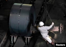 FILE - An employee works at the Baosteel Group Corp. factory in Shanghai.