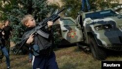Un muchacho juega con un fusil de asalto Kalashnikov en Soledar, al este de Ucrania.