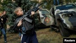 Хлопчик з автоматом Калашнікова у м.Соледар, 27 вересня 2014 року. Діти перебувають під наглядом дорослих, тримаючи зброю.