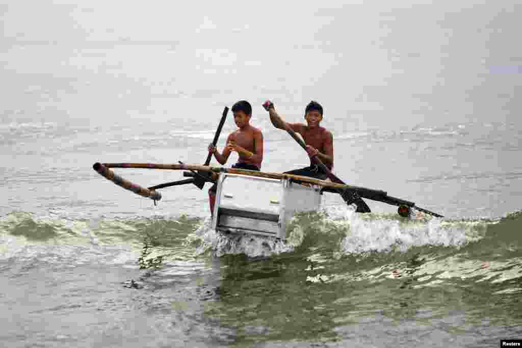 Boys maneuver their boat, made from a broken fridge and bamboo, to the beach in Tanauan, Philippines. After losing their boats and houses in the Typhoon Haiyan, fishermen of a destroyed village in Tanauan started building two-seated boats made of abandoned refrigerators and some wood.