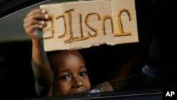 """Dečak u automobilu nosi znak """"Pravda"""" na protestu protiv rasizma u Ričmondu, Virdžiniji"""