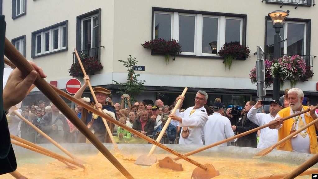 Cooks and volunteers stir eggs on an oversize pan at the 22nd Giant Omelet event in Malmedy, Belgium, August 15, 2017. (AP Photo/Daniela Berretta)