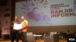 Ketua Umum AJI Indonesia Eko Maryadi (kiri) dan Direktur Kepesertaan Jamsostek Junaedi usai penandatangan MOU perlindungan kepada kontributor, stringer dan pekerja lepas media di daerah. (VOA/Andylala Waluyo)