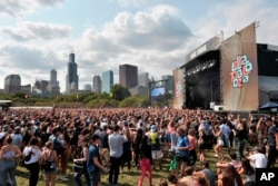 Fans watch performances at Lollapalooza in Grant Park, Aug 6, 2017 in Chicago. According to reports, the Las Vegas gunman also reserved rooms in Chicago, overlooking the Lollapalooza festival, but he did not check in.
