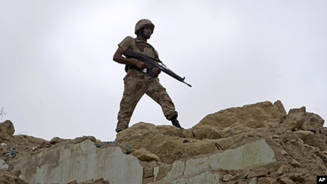 A Pakistani paramilitary soldier observes the area from a hilltop after security forces took control of a troubled area of Karachi, Pakistan, July 9, 2011