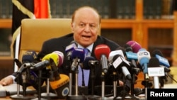 Yemen's President Abd-Rabbu Mansour Hadi speaks as he holds an agreement (L) signed between the government and Houthi rebels, in Sanaa, Sept. 21, 2014.