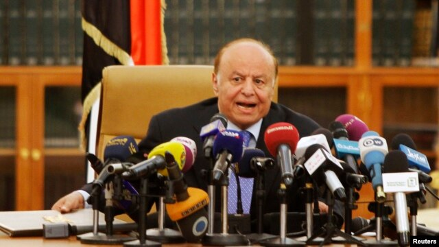 FILE - Yemen's President Abd-Rabbu Mansour Hadi speaks as he holds an agreement (L) signed between the government and Houthi rebels, in Sanaa, Sept. 21, 2014.